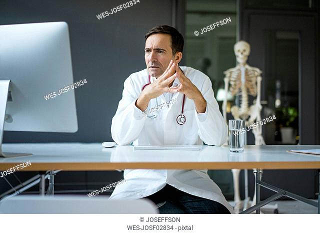 Serious doctor sitting at desk in medical practice with skeleton in background