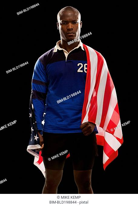 African American rugby player wrapped in American flag