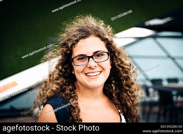Close up Happy Young Woman, Wearing Eyeglasses, with curly hair, Showing Toothy Smile at the Camera Against city Background