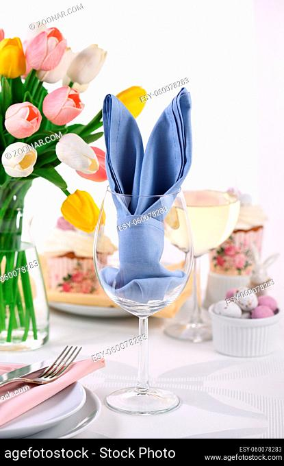A napkin folded in the form of hare (rabbit) ears in a glass, the concept of setting a festive table in honor of Easter