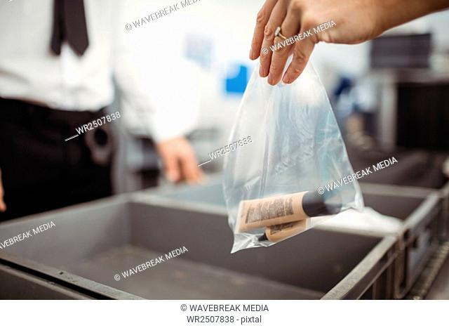 Passenger putting plastic bag into tray for security check