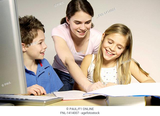 Brother and sisters studying and smiling