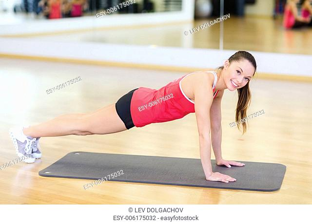 fitness, sport, training, gym and lifestyle concept - smiling woman doing plank on mat in gym