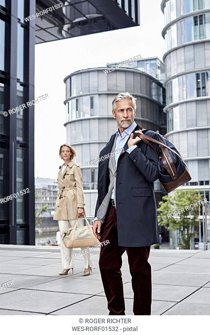 Germany, Duesseldorf, two fashionable business people with traveling bags