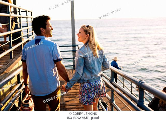 Rear view of young couple strolling on pier, Santa Monica, California, USA