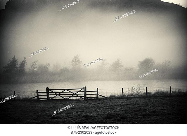 Closeup of a fence with a gate on the bank of the river Wharfe in a foggy early morning. Grassington, Yorkshire Dales, England, UK