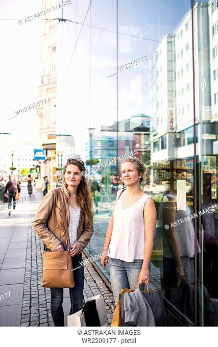 Young female friends with shopping bags on sidewalk