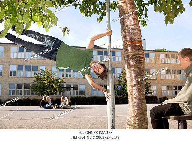 Teenage boy swinging lamp post