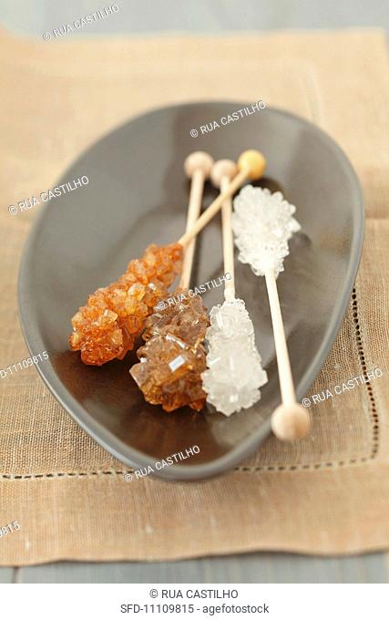 Brown and white rock sugar sticks in a bowl