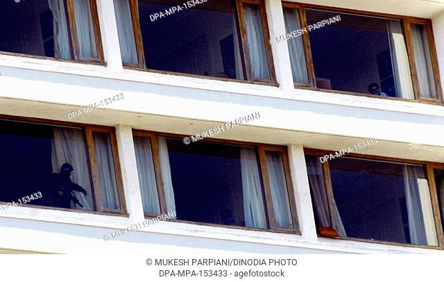 National Security Guard NSG commando opening curtain to indicate room is safe from Deccan Mujahideen terrorists at Oberoi (Trident hotel) Nariman Point ; Bombay...