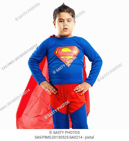 Boy dressed as a superman standing with his arm akimbo