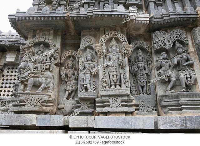 Ornate wall panel reliefs depicting Shiva-Parvati on the left, Brahma in the centre and other deities, North wall, Kedareshwara temple, Halebidu, Karnataka