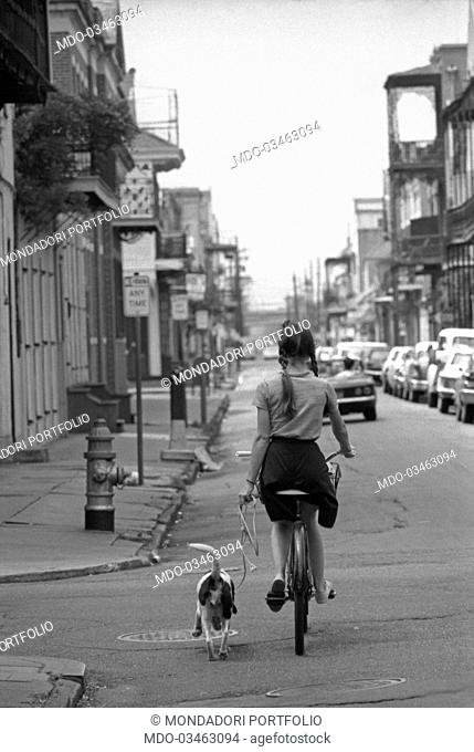 A girl biking with a dog on the leash on her left hand. Houston, 16th October 1965