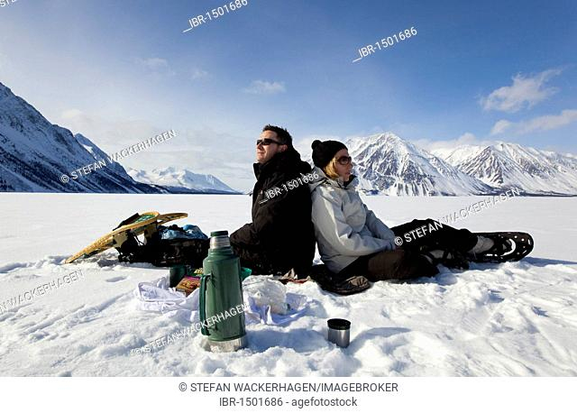 Frozen Kathleen Lake, young couple, snow shoes, resting, St, Elias Mountains behind, Kluane National Park and Reserve, Yukon Territory, Canada