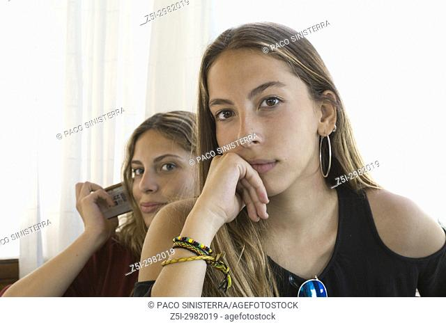 Interior portrait of two young girls with thoughtful expression