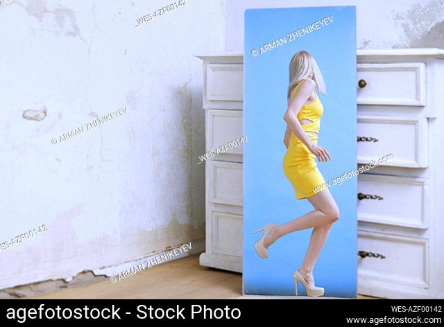 Young woman seen in mirror reflection against white wooden drawer