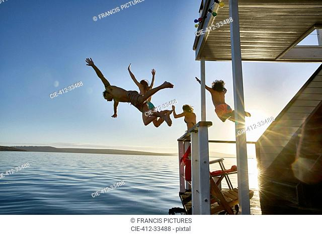 Young adult friends jumping from summer houseboat into sunny ocean