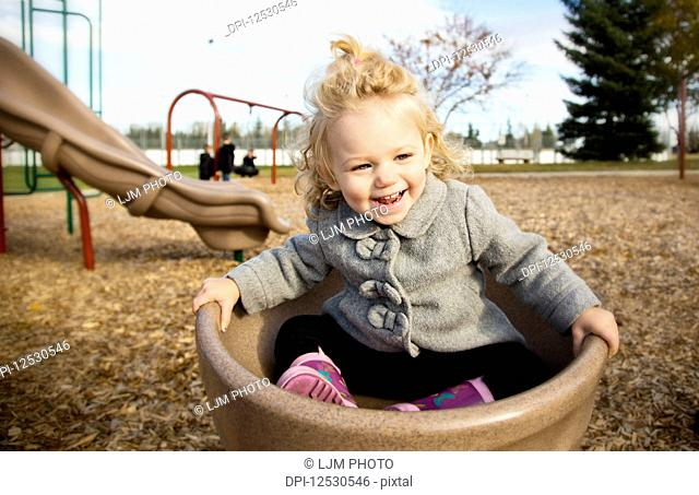 A cute young girl spinning in a saucer on a playground during the fall season; Spruce Grove, Alberta, Canada