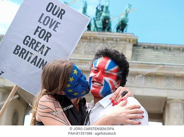 """A young couple whose faces are painted in the colours of European and British flags, posing with a sign """"""""Our Love For Great Britain"""""""" during a Kiss Marathon at..."""