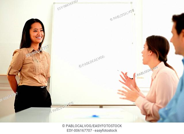 Portrait of a young asiatic businesswoman giving a conference to colleagues on office during a meeting