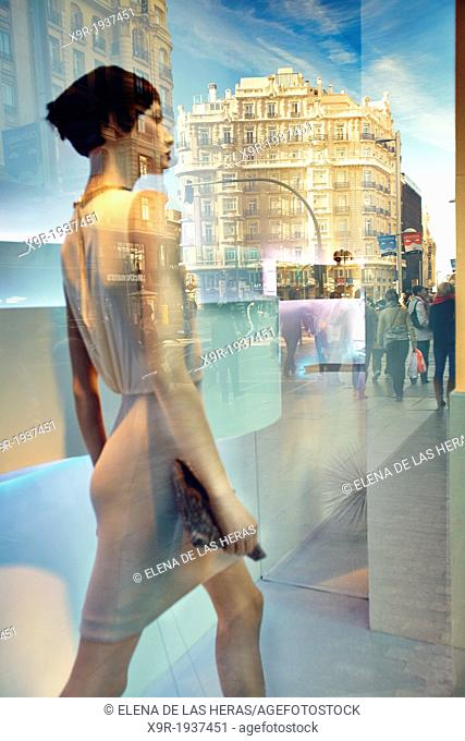 Mannequin and reflections at a window shop in Gran Via avenue. Madrid. Spain