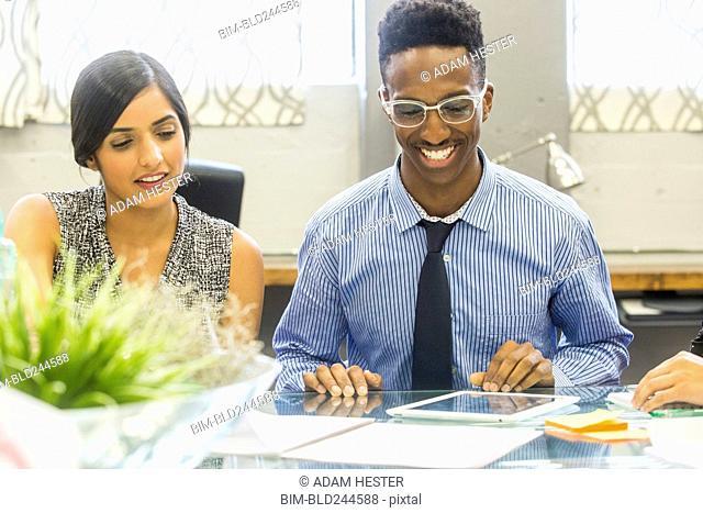 Smiling people using digital tablet in meeting
