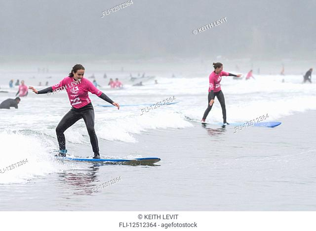 Girls learning to surf at Cox Bay Beach, Pacific Rim National Park, Vancouver Island; Tofino, British Columbia, Canada