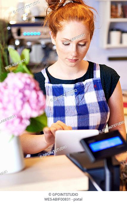 Young woman working in a cafe using tablet