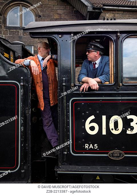 The driver of a vintage steam engine locomotive, North Yorkshire Moors Railway, on the North Yorkshire Moors, Yorkshire, UK