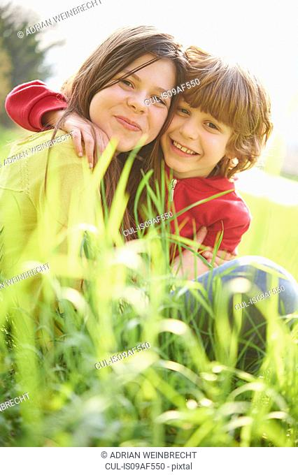 Sister and younger brother sitting in grassy field