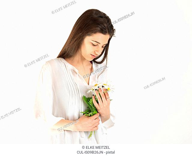 Studio portrait of young woman gazing at bunch of daisies