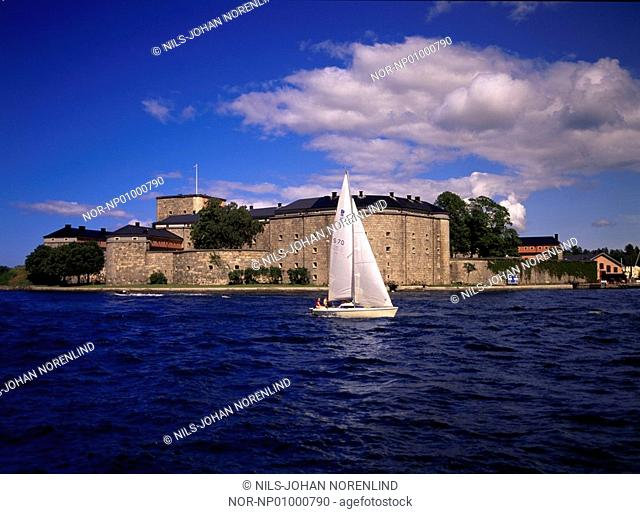 A sailboat on the sea and castle in the background