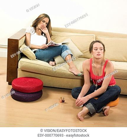 pictures in a living room of two young girls sitting on a couch getting bored