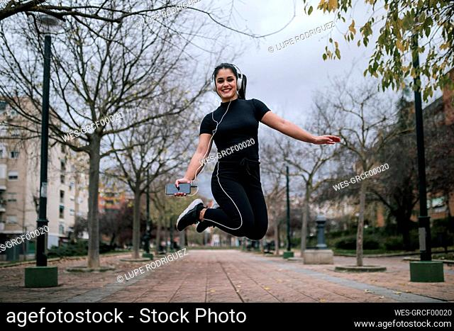 Portrait of young woman in black sportswear jumping in the air while listening music with headphones
