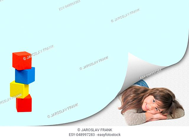 Page with curl effect and smiling cute little girl lying in an exposed corner looking at the camera. Colorful tower of wooden cubes is ready for your text