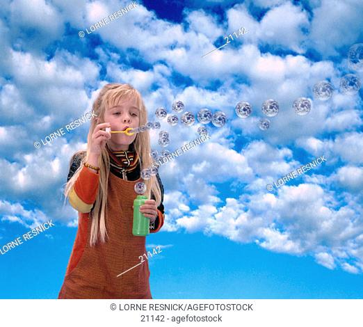 Young girl blowing earth bubbles
