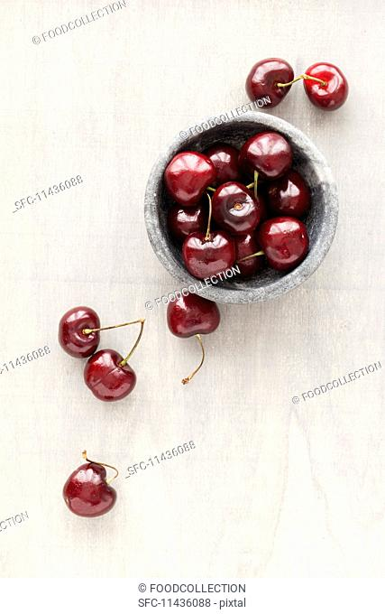 Fresh cherries in a marbled bowl and next to it