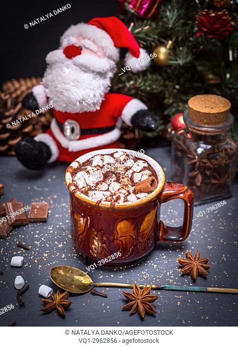 hot cocoa with marshmallow in a brown ceramic mug on a black background, behind a textile Santa Claus and Christmas tree