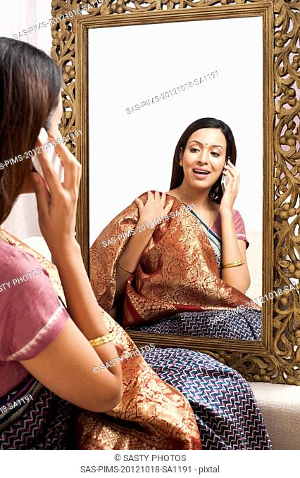 Reflection of a woman in mirror trying a sari on herself and talking on a mobile phone