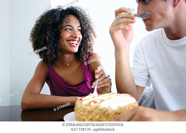 Hugry couple eating cake with fridge