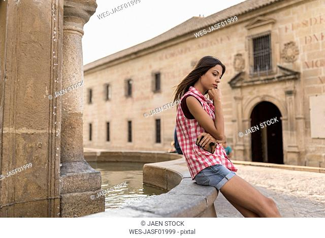 Spain, Baeza, pensive young woman sitting on edge of fountain