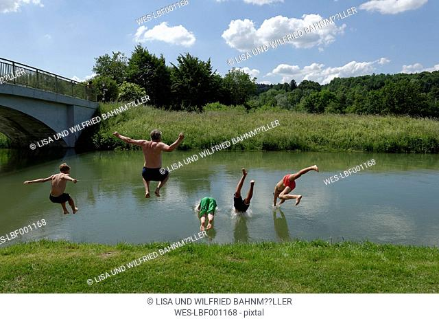 Germany, Bavaria, kids and man jumping into River Loisach
