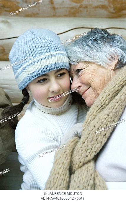 Grandmother and granddaughter, smiling, cheek to cheek, portrait