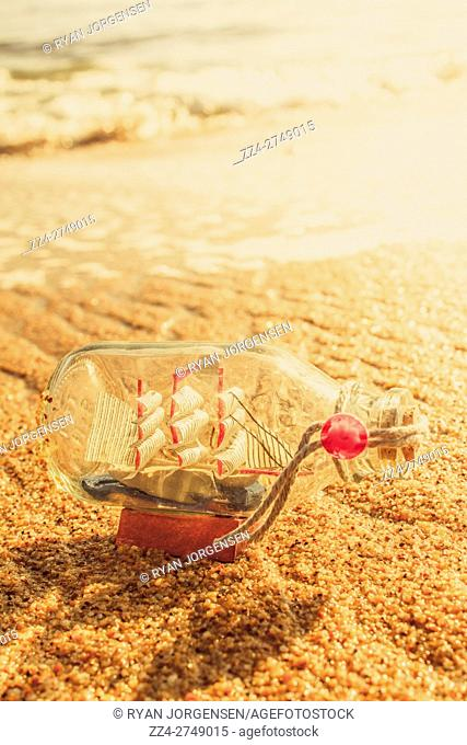 Maritime conceptual artwork of a nautical glass bottle boat by the sea. Still-life journey
