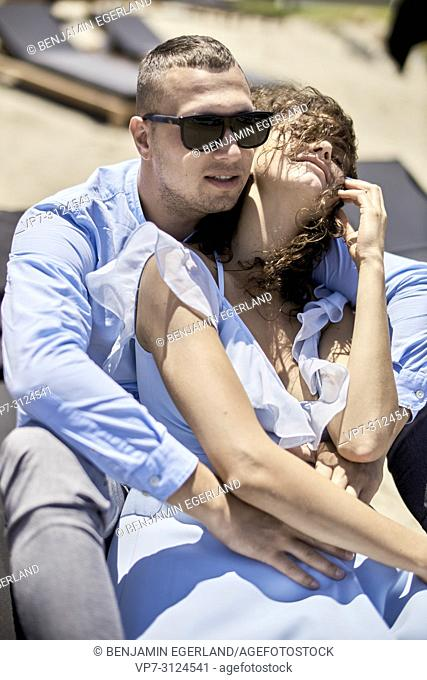 man embracing woman, on sunbeds, holidays, love, affair, sensual, couple, flirt, summer