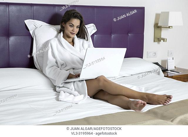 Wonderful young brunette in bathrobe chilling on bed in hotel room and surfing modern laptop with smile