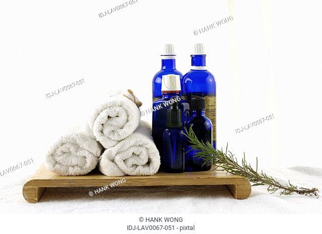 Massage oil bottles near bundles of towels