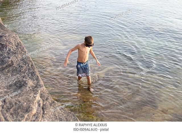 High angle view of teenage boy paddling in Lake Superior, Au Train, Michigan, USA