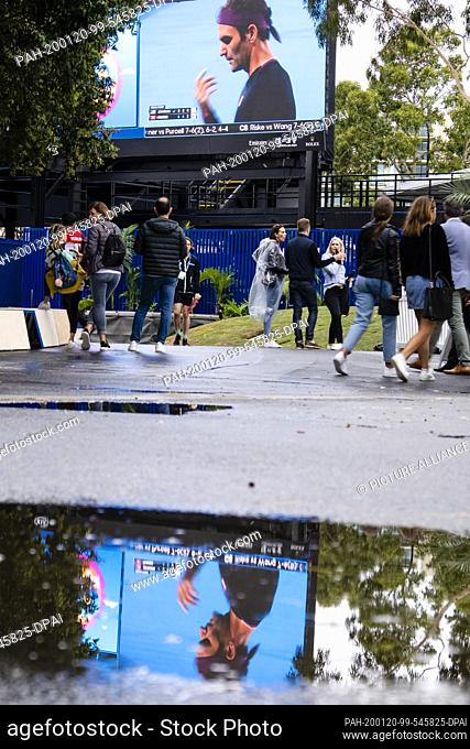 20 January 2020, Australia, Melbourne: Tennis: Grand Slam, Australian Open. The image of a video screen with the face of Roger Federer is reflected in a puddle