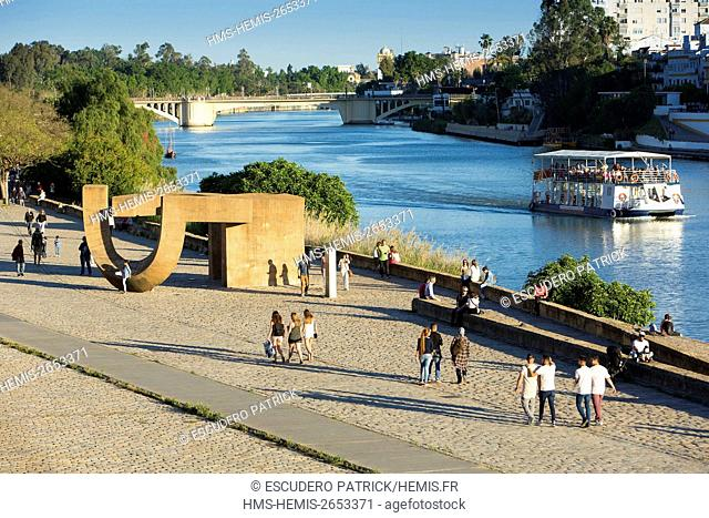 Spain, Andalucia, Sevilla, people walking by the riverside of the Guadalquivir river below the Paseo de Cristobal Colon